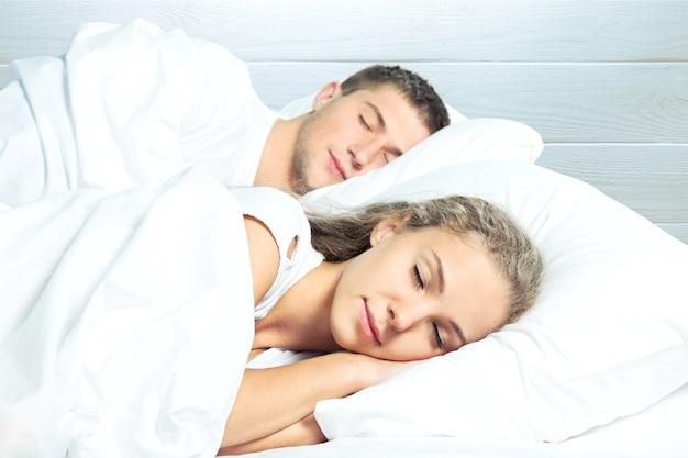 Jovem casal dormindo na cama do quarto