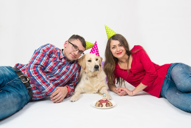 Jovem casal e um cão retriever na tampa do aniversário e bolo com vela.