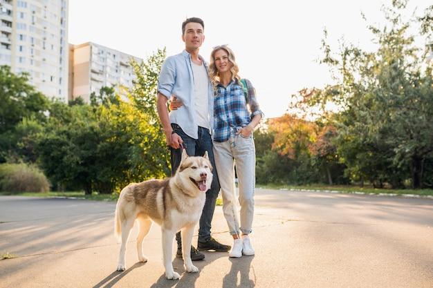 Jovem casal elegante andando com o cachorro na rua. homem e mulher felizes juntos com raça husky
