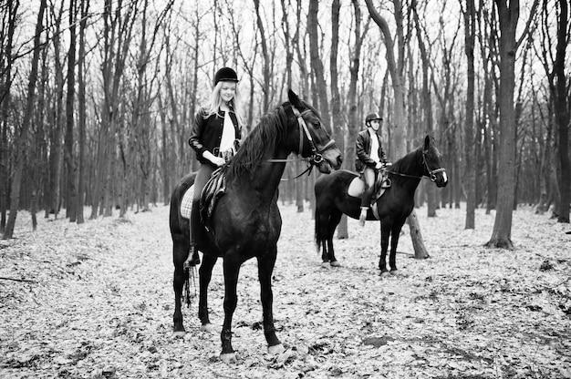 Jovem casal elegante, andar a cavalo na floresta de outono