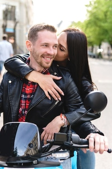 Jovem casal elegante com uma motocicleta em uma rua da cidade