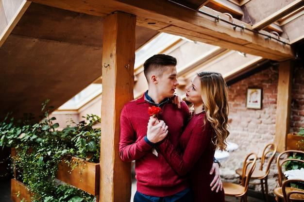 Jovem casal elegante lindo em um vestido vermelho em história de amor no café vintage com grandes janelas no telhado