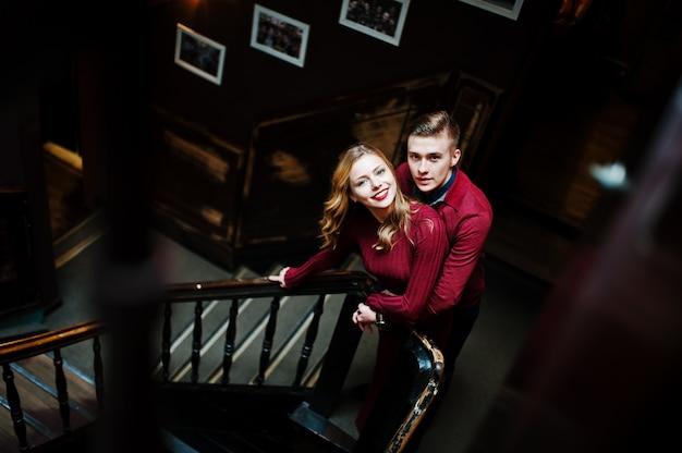 Jovem casal elegante lindo em um vestido vermelho na grande escada vintage de madeira