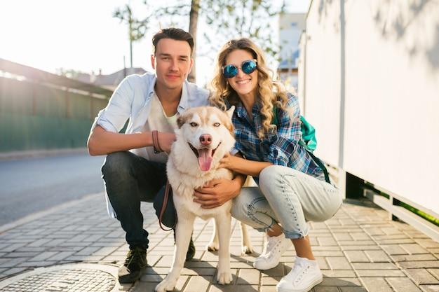 Jovem casal elegante posando com cachorro na rua
