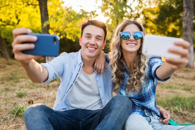 Jovem casal elegante sentado no parque, homem e mulher, família feliz juntos
