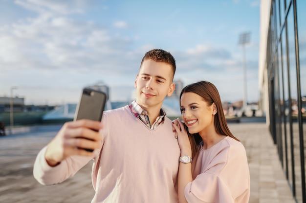 Jovem casal elegante tomando selfie no telhado
