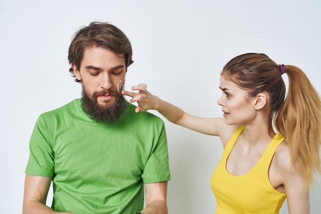 Jovem casal em camisetas multicoloridas, higiene, cuidados faciais, manhã saudável