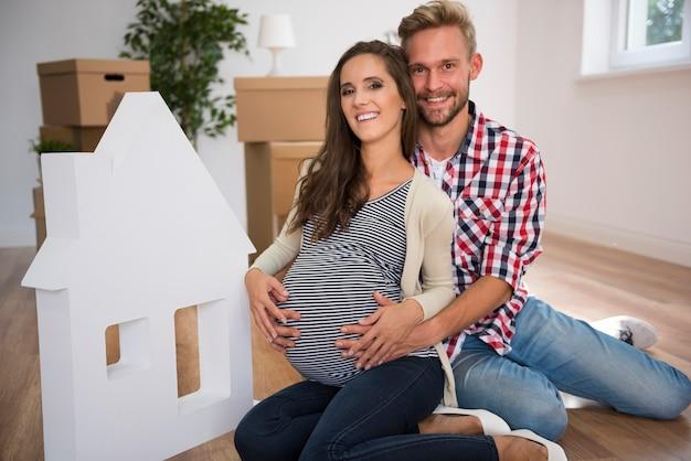Jovem casal em casa ao lado de casa branca