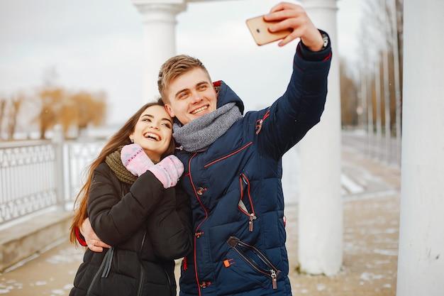 Jovem casal em casacos de inverno e cachecóis em pé em um parque de neve e usando o telefone