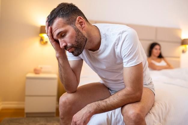 Jovem casal em crise de relacionamento, chateado homem e mulher sentados separados na cama