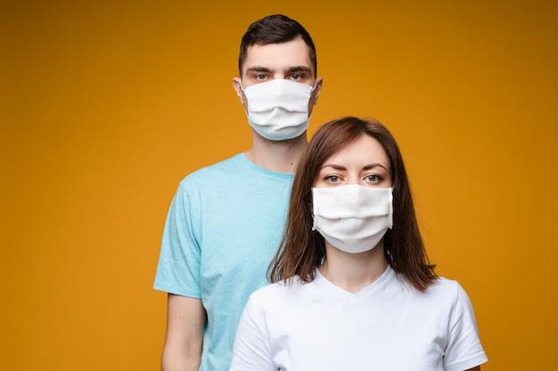Jovem casal em máscaras assépticas