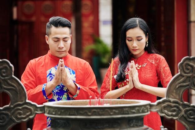 Jovem casal em pé com os olhos fechados e de mãos dadas em um gesto de orar em frente à antiga urna de bronze com incensos