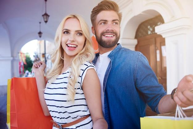 Jovem casal em pé com sacolas de compras