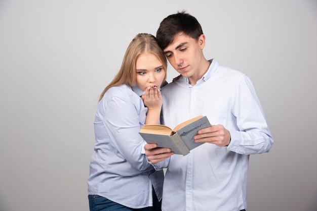 Jovem casal em pé e lendo um livro na parede cinza
