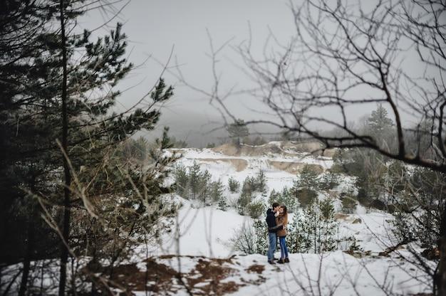 Jovem casal em pé em um campo nevado de inverno.