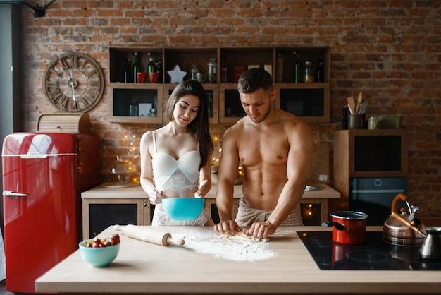 Jovem casal em roupa interior cozinhando na cozinha. homem e mulher nus preparando café da manhã em casa, preparação de comida sem roupa