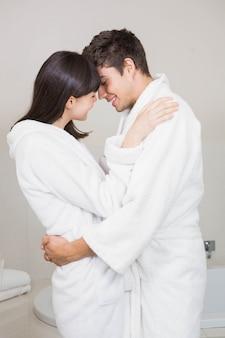 Jovem casal em roupão de pé frente a frente em casa no banheiro