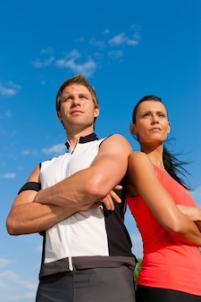 Jovem casal em roupas esportivas, posando na frente da câmera