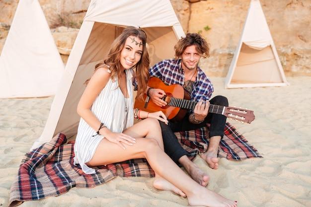 Jovem casal em tenda na praia