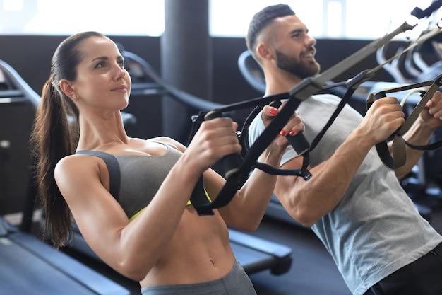 Jovem casal em treinamento corporal com trx no ginásio.