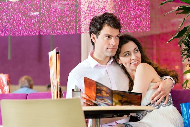 Jovem casal em um café ou sorveteria, ela mostrando algo em uma bolsa