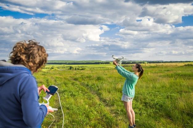 Jovem casal em um campo lança o drone para o céu