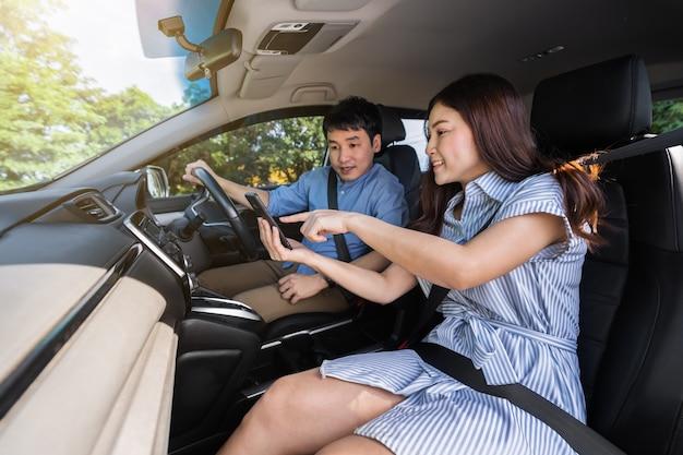Jovem casal em um carro olhando o mapa no smartphone para orientação