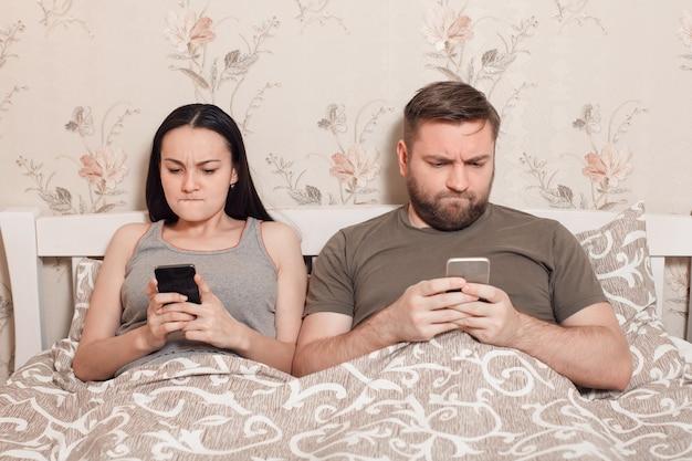 Jovem casal em uma cama com telefones celulares