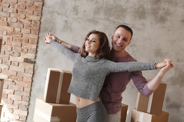 Jovem casal embalando coisas para se mover e dançar