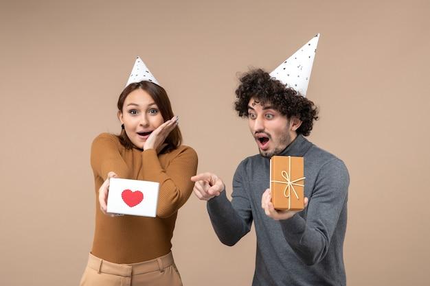 Jovem casal emocional e energético usa poses de chapéu de ano novo para a câmera. garota mostrando um coração e um cara com um presente