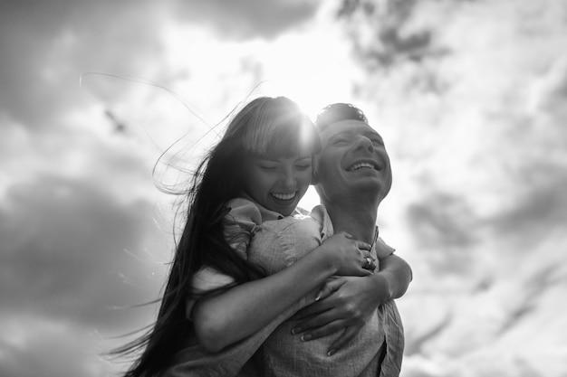 Jovem casal emocionalmente se divertindo ao ar livre.