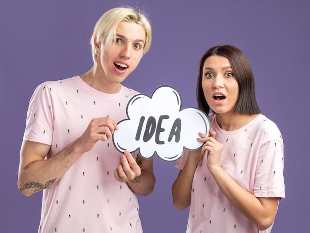Jovem casal empolgado e impressionado com uma mulher de pijama segurando uma bolha de ideias isolada na parede roxa