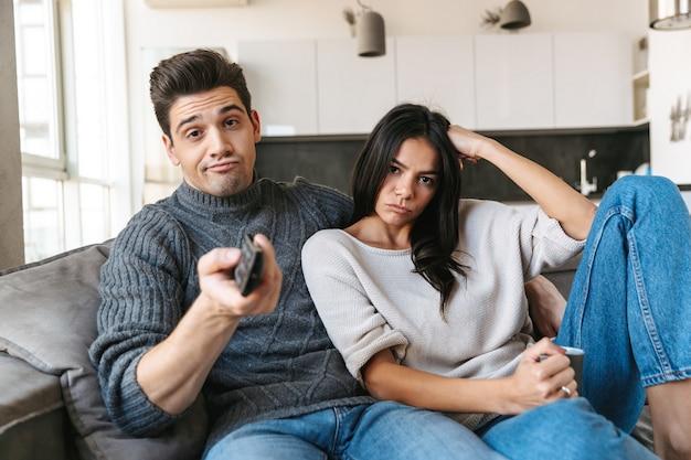 Jovem casal entediado sentado em um sofá em casa, assistindo tv