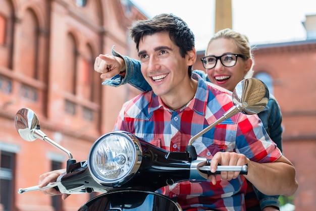 Jovem casal entusiasmado passeando de scooter por berlim