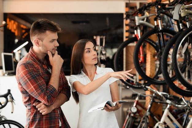 Jovem casal escolhe bicicleta olhar catálogo na loja