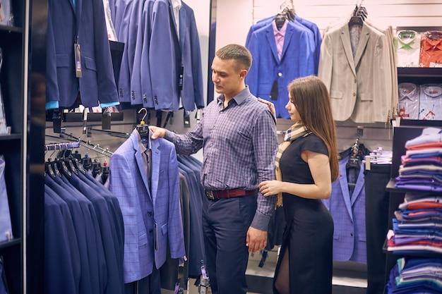 Jovem casal escolhe uma jaqueta na loja.