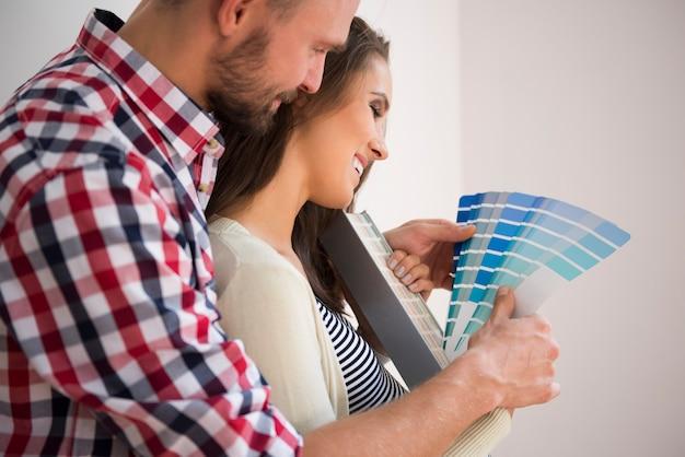 Jovem casal escolhendo a cor do quarto do bebê Foto gratuita