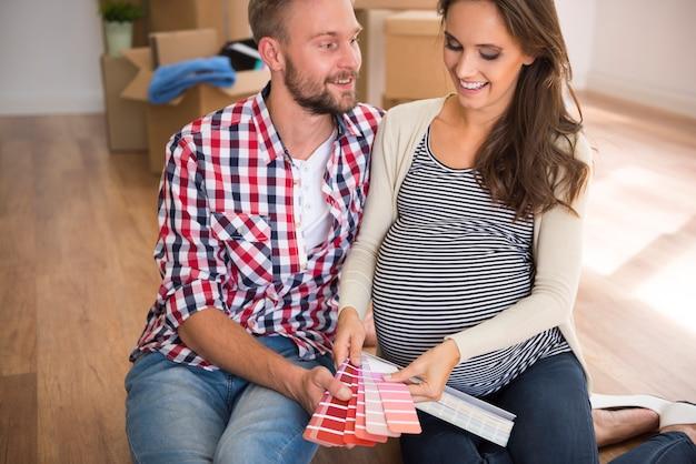 Jovem casal escolhendo a cor do quarto do bebê