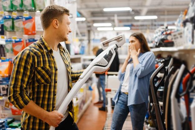 Jovem casal escolhendo aspirador de pó na loja de eletrônicos. homem e mulher comprando eletrodomésticos no mercado