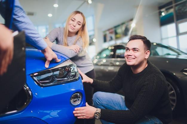 Jovem casal escolhendo carro novo para comprar na loja da concessionária.