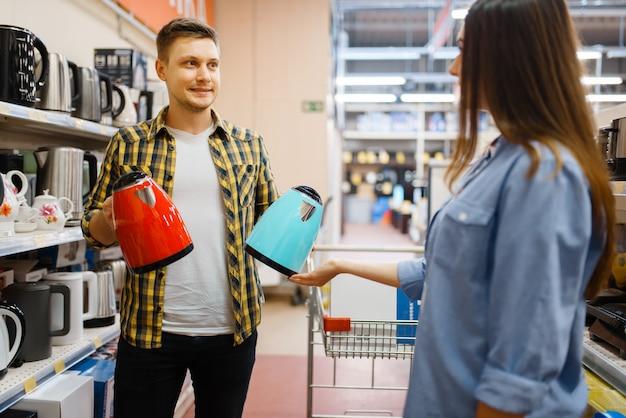 Jovem casal escolhendo chaleira elétrica em loja de eletrônicos. homem e mulher comprando eletrodomésticos no mercado