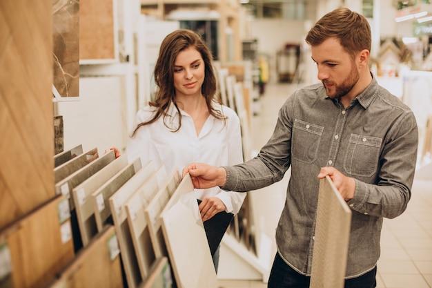 Jovem casal escolhendo ladrilhos no mercado de construção