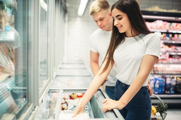 Jovem casal escolhendo produtos congelados no supermercado. clientes em loja de alimentos