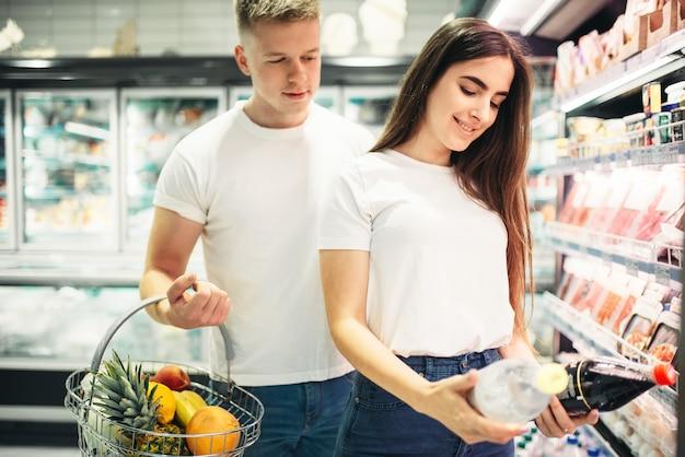 Jovem casal escolhendo produtos em supermercado