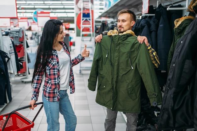 Jovem casal escolhendo roupas quentes no supermercado. clientes masculinos e femininos nas compras da família. homem e mulher comprando produtos para a casa