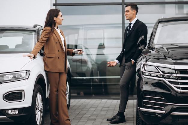 Jovem casal escolhendo um carro em uma sala de exposições