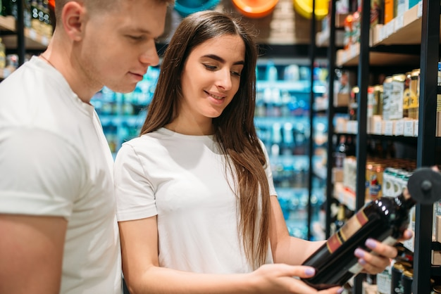 Jovem casal escolhendo vinho na seção de álcool no mercado. clientes em loja de alimentos