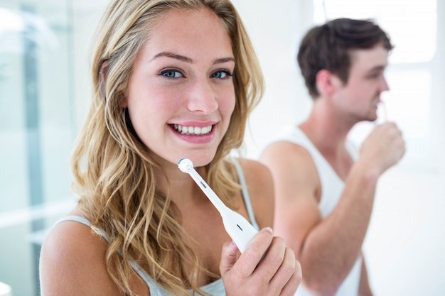 Jovem casal escovando os dentes em casa no banheiro