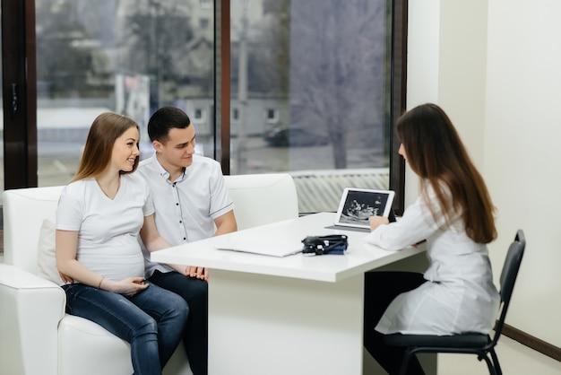 Jovem casal esperando bebê consultar ginecologista após um ultra-som.