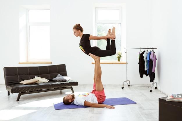 Jovem casal esportivo bonito praticando ioga asanas em casa.